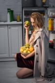 junge Frau im Trenchcoat hält Schüssel mit frischen Früchten neben geöffnetem Kühlschrank