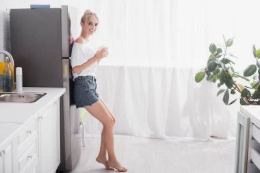 Barefoot blonde woman standing near refrigerator with cup of tea stock vector