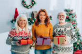 happy senior couple with daughter looking at camera while holding gift boxes