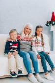 Lächelnde Seniorin und Enkel blicken in die Kamera, während sie gemeinsam auf dem Sofa sitzen
