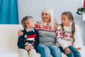 Lächelnde Seniorin spricht mit Enkeln, während sie gemeinsam auf dem Sofa sitzt