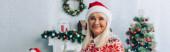 panoráma lövés boldog idős nő télapó kalap nézi kamera közelében karácsonyfa a háttérben