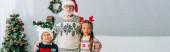 Panoramaaufnahme des Großvaters, der seine Enkel in Weihnachtsmützen umarmt