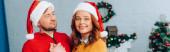 horizontal image of woman in santa hat smiling at camera while embracing husband on christmas