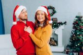 glückliche Frau mit Weihnachtsmütze blickt in die Kamera, während sie ihren Mann an Weihnachten umarmt