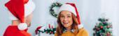 panoramic shot of happy woman in santa hat looking at camera near husband