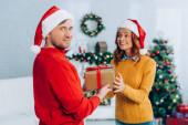 mosolygós férfi télapó kalap nézi a kamera, miközben bemutatja ajándék doboz izgatott feleség