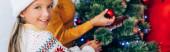 Website-Header des glücklichen Mädchens, das in die Kamera schaut, während es den Weihnachtsbaum mit der Familie schmückt