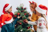 glückliche Familie in Weihnachtsmützen schmücken Weihnachtsbaum zusammen zu Hause