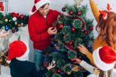 šťastná rodina v Santa klobouky zdobení vánoční stromeček společně doma