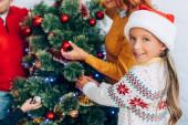 glückliches Mädchen mit Weihnachtsmütze, das in die Kamera schaut, während es mit der Familie den Weihnachtsbaum schmückt