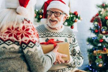 Selective focus of senior woman presenting gift box to cheerful husband stock vector