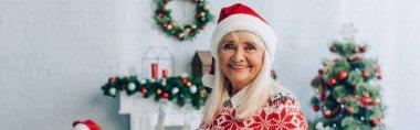 Panoramic shot of happy senior woman in santa hat looking at camera near christmas tree on background stock vector