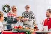Selektiver Fokus älterer Menschen mit Truthahn in der Nähe von Familie und Festtafel