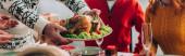Panoráma felvétel férfi felszolgáló pulyka ünnepi asztal közelében család otthon