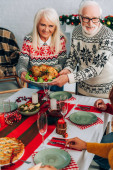 Smiling grandparents serving turkey on festive table near family at home