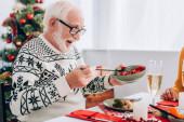 Idősebb férfi szemüvegben, kezében tál zöldséggel, ül az ünnepi asztalnál