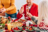 Oříznutý pohled na ženu a muže držící sklenice se šampaňským, sedící poblíž rodiny u stolu