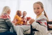 Selektivní zaměření usměvavé dívky dívající se do kamery, sedí u stolu s rodinou