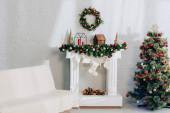 Rozkládací pohovka s přikrývkou u krbu s vánoční punčochy a zdobené borovice