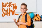 Photo Schoolboy holding digital tablet near back to school illustration