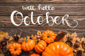 Photo top view of autumnal decoration and pumpkins near well hello october lettering on wooden background