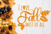 vrchní pohled na podzimní dekorace a hrozny v blízkosti i love podzim nejvíce ze všech nápisů na bílém dřevěném pozadí