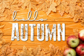 top view of ripe apples and leaves near hello autumn lettering on wooden background
