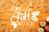 top view of ripe apples and autumnal foliage near i love fall most of all lettering on wooden background