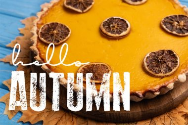 Close up view of decorated pumpkin pie with golden foliage near hello autumn lettering on blue background stock vector