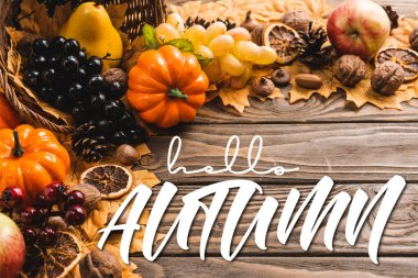 Autumnal harvest in basket on foliage near hello autumn lettering on wooden background stock vector