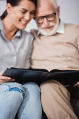 adult woman with elderly father browsing photo album on blurred background