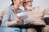 smiling woman looking at photos while sitting near aged father on blurred background