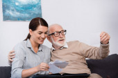 smiling woman with elderly father looking at family photos together at home