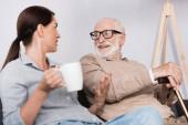 brunetka žena drží čaj a gesta, zatímco mluví s veselým starším otcem