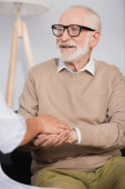 smiling senior man holding hands with social nurse at home on blurred foreground