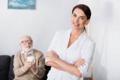 fröhliche Sozialarbeiterin lächelt in die Kamera, während sie mit verschränkten Armen neben einem alten Mann steht, der eine Tasse Tee hält