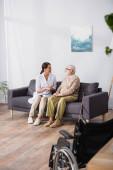 Sozialarbeiterin spricht mit älterem Mann, der mit Rollstuhl auf Sofa sitzt