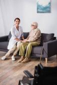 fröhliche Altenpflegerin hält Händchen mit einem alten Mann, der zu Hause auf dem Sofa sitzt