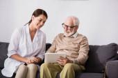 Lächelnder älterer Mann mit digitalem Tablet in der Nähe fröhlicher Altenpflegerin zu Hause