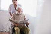 Altenpfleger nahe älterer Behinderter liest Zeitung im Rollstuhl