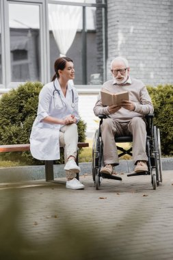 Handicapped aged man reading book in wheelchair near social worker sitting on bench on blurred foreground stock vector