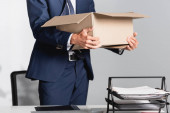 Vágott kilátás kirúgott üzletember kezében kartondoboz közelében papírok elmosódott előtér
