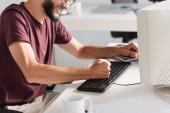 Oříznutý pohled na stresovaného podnikatele mlátícího počítačovou klávesnicí v kanceláři