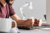 Oříznutý pohled na stresovaného podnikatele bití počítačové klávesnice s šálkem a shlukem papíru na rozmazané popředí