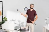 Podnikatel drží golfovou hůl v blízkosti počítače na rozmazané popředí v úřadu