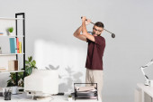Angry businessman holding golf club near computer and documents on office table