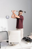 Stressed businessman holding golf club near computer and papers on blurred foreground in office