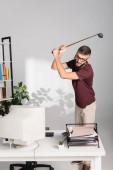 Rozzlobený podnikatel s golfovou holí stojící poblíž počítače a dokumenty na rozmazaných popředí v úřadu