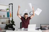 Stresszes üzletember sikoltozik, miközben laptopot dobál az irodai asztalra.